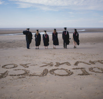 graduates walking across the beach, with Thank You/Diolch written in the sand