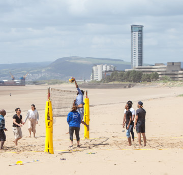 Students on the beach playing volley ball.