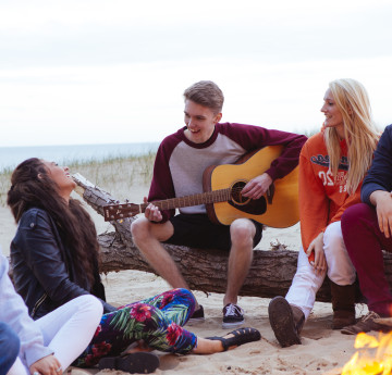 Students on the beach around a campfire with a boy playing a guitar.