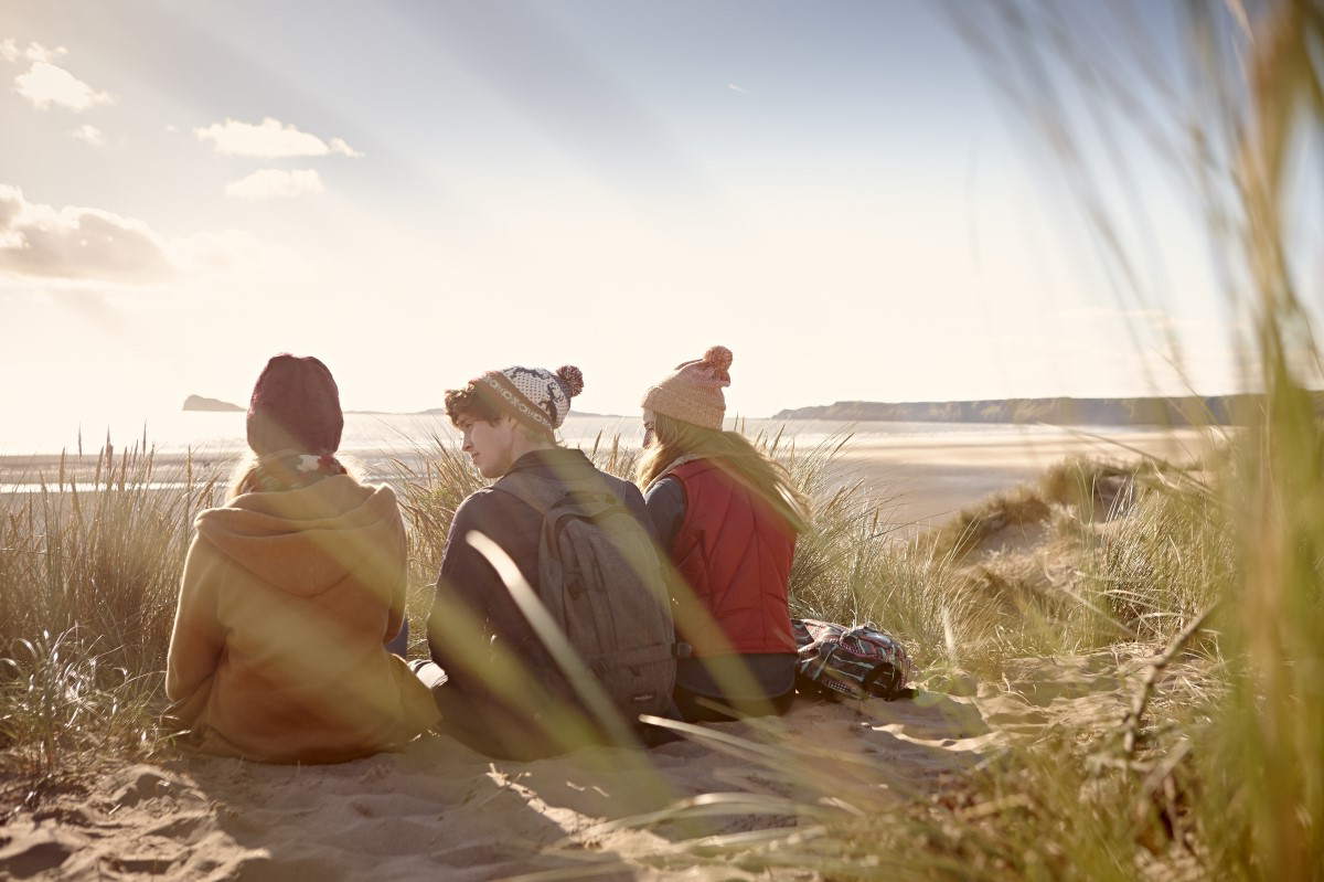 Two female students and one male student sitting in the sane dunes and looking out to the sea.