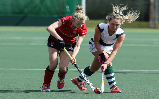 Two Hockey players battling over the ball.
