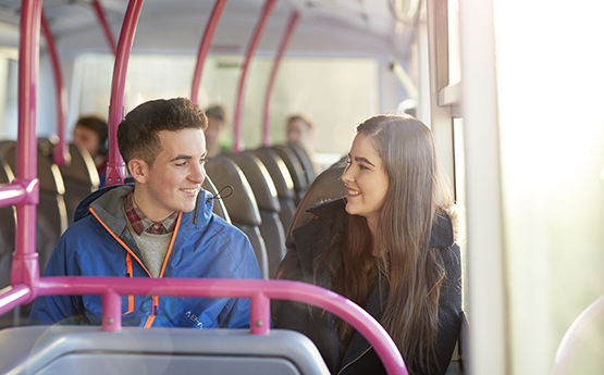 Two students sitting on the bus and smiling at each other.